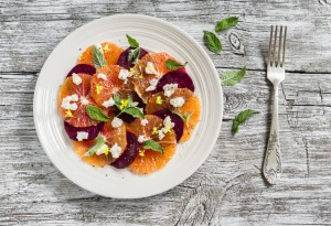 fresh salad with oranges, beets and feta cheese on a white plate on a light wooden surface