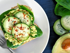Avocado toast with cucumber, spinach and whole grain bread on white plate against a slate background