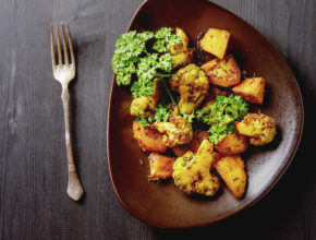 Traditional Indian Aloo Gobi fish with potato, cauliflower and spices on a brown plate, fork. Dark wood background